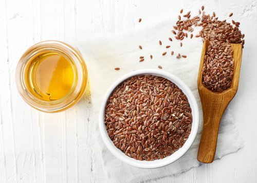 flaxseeds in a small serving bowl with a wooden spoon and a side of flaxseed oil